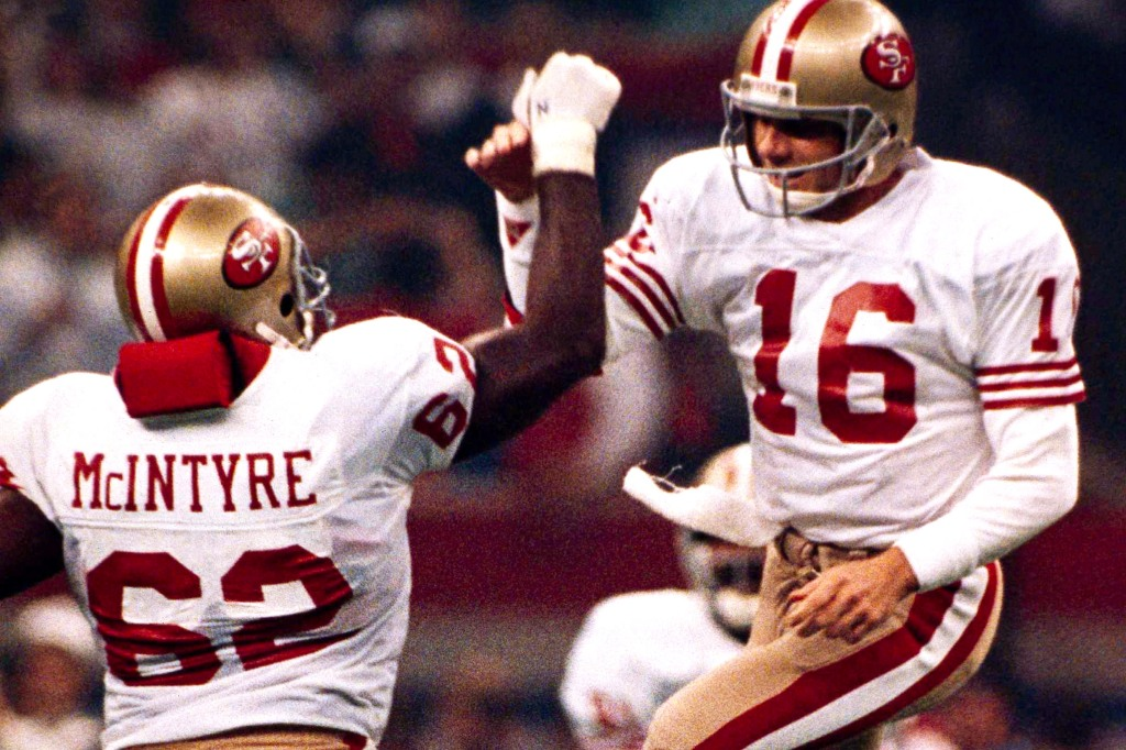San Francisco 49ers quarterback Joe Montana (16) is walking on air after a third quarter touchdown in Super Bowl XXIV, Sunday, Jan. 28, 1990 in New Orleans Montana, who was awarded the MVP trophy for his record-setting performance is congratulated by teammate Guy McIntyre. (AP Photo/Mark Duncan)