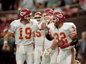Kansas City Chiefs quarterback Joe Montana (L) congratulates Chiefs running back Marcus Allen  after his fourth touchdown in their game against the Houston Oilers in the Astrodome in Houston, Texas January 16, 1994 . The Oilers lost the game 28-20.   REUTERS/Gary Cameron   BEST QUALITY AVAILABLE - RTR2UVON