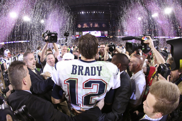 New England Patriots quarterback Tom Brady, the game's MVP, faces a throng of reporters and photographers on the field after his team's Super Bowl XLIX victory.